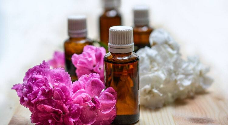 Bottles of essential oils next to flowers on table