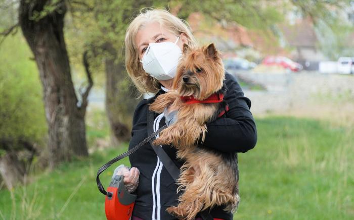 Woman wearing mask holding dog outside